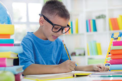 Little scientist with glasses writing Stock Photography