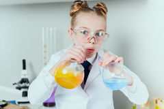 Little scientist in lab coat and protective eyeglasses making experiment with reagents in flasks Royalty Free Stock Photos