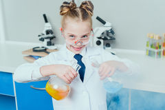 Little scientist in lab coat and protective eyeglasses making experiment with reagents in flasks Stock Image