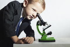 Little scientist looking in microscope.little boy in tie.stylish child.Schoolboy Royalty Free Stock Images