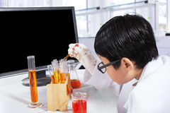 Little scientist makes chemistry experiments. Little boy studying as a scientist while doing experiments with chemical in the laboratory Stock Image