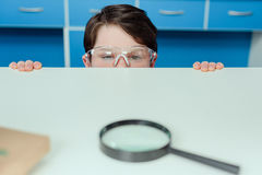 Little scientist in protective eyeglasses looking at magnifier lying on table Stock Photo