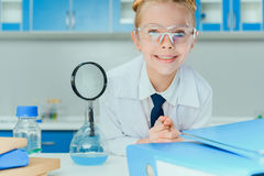 Little scientist in protective eyeglasses smiling at camera Royalty Free Stock Photography