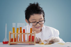Little scientist touches liquid chemical Stock Photo
