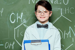Little scientist in white coat and protective eyeglasses holding clipboard and smiling at camera Stock Images