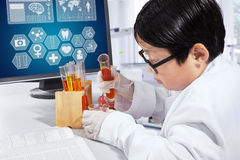 Little scientist working in the laboratory. Little boy working in the laboratory as a scientist and make chemical experiments Royalty Free Stock Images