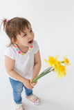 Little screaming girl holding flowers. Royalty Free Stock Images