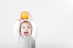 Little screaming girl with orange Royalty Free Stock Image