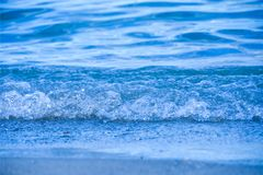Little sea blue wave washes up to shore. Copy space stock photography