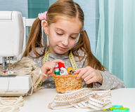 Little seamstress with threads in basket and Stock Photos