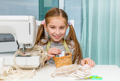 Little seamstress with threads in basket and. Little seamstress sitting at the table with threads in basket and sewing machine Royalty Free Stock Photos