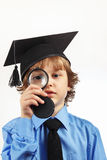 Little serious boy in academic hat with a magnifying glass on white background Stock Photography