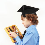 Little serious boy in academic hat with old abacus on white background Stock Images