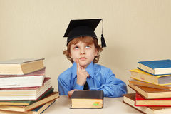 Little serious boy in academic hat among old books Royalty Free Stock Images