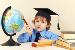 Little serious boy in academic hat with a pen showing on geographical globe Stock Photography