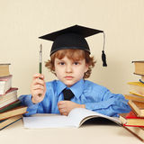Little serious boy in academic hat with rarity pen among old books. Little serious boy in academic hat with rarity pen among the old books Stock Image