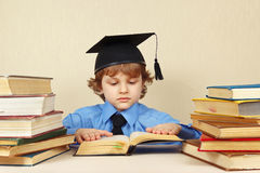 Little serious boy in academic hat reading old books Stock Images