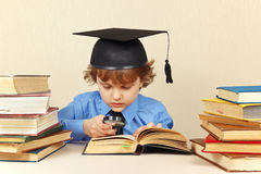 Little serious boy in academic hat reading an old books with magnifying glass Stock Image