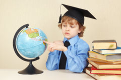 Little serious boy in academic hat showing on globe among old books Stock Image