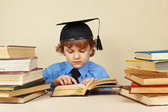 Little serious boy in academic hat studies old books Stock Photos