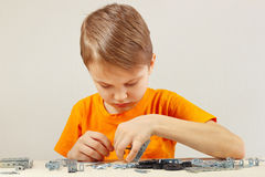 Little serious boy plays with mechanical constructor at table Royalty Free Stock Images