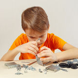 Little serious boy plays with mechanical kit at table Stock Photo