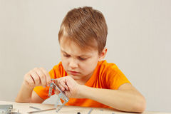 Little serious boy plays with mechanical starter kit at table Stock Image