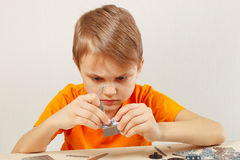 Little serious boy plays with metal constructor at table Stock Images