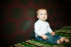 Little serious boy sitting near the wall Stock Photography