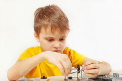 Little serious engineer plays with mechanical constructor at table Stock Photo