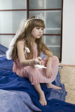 Little serious girl in angel wings. Diadem with magic wand sitting after birthday party Royalty Free Stock Image