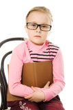 The little serious girl in glasses with a book Royalty Free Stock Photos