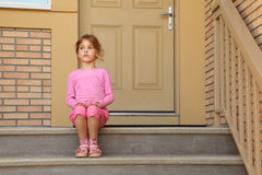 Little serious girl sits on stairs near door Stock Photos