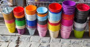 Little set of buckets of various colors. In a market place stock image