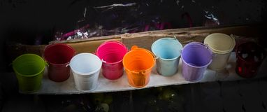 Little set of buckets of various colors. In a market place royalty free stock photo