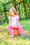 Little seven year old girl sitting on the ball. Little seven year old girl is sitting on the ball Stock Photo