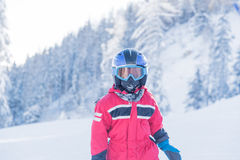 Little seven years old skier in red suit blue helmet and goggles Royalty Free Stock Photos