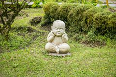 Shaolin Monk Statue in a Garden. Little Shaolin Monk Garden Statue in a Garden. Shaolin Monk Pensive stock photography