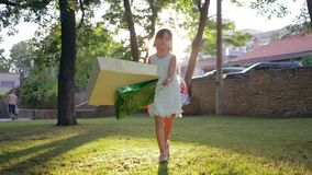 Little shopper girl relish new buys after visiting fashion boutiques and waving packages on nature in bright sunshine. Little shopper girl relish new buys after stock video