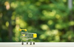 Little shopping cart on forest background. Little shopping cart on a shiny green forest background Royalty Free Stock Photography