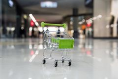 Little shopping trolley on tile floor of empty shopping centre. Concept of buying things in mall. Toy shopping cart at blur. Supermarket background. Purchasing royalty free stock photo