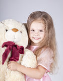 Little shouting girl embraces bear cub. Royalty Free Stock Photography