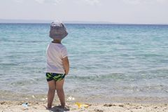 A little shy boy with hat standing in the sand near water and lo stock image