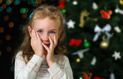 Little shy girl. Over christmas decorations stock photography