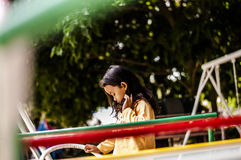 Little shy girl. The girl sit on a new big swing in Korat, Thailand stock photography