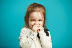 Little shy girl smiles and covers her mouth with hands, expresses embarrassment and indecision, emotional photo of. Children shyness on blue isolated background stock photography