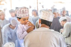 Little shy boy leaning against the shoulder of his father. Stock Image