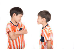 Little sibling boy fighting brother with bad mood on white background Stock Images