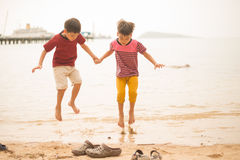 Little sibling boy jumping over the beach Stock Photography