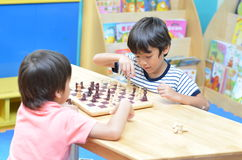 Little sibling boy playing chess Stock Photography